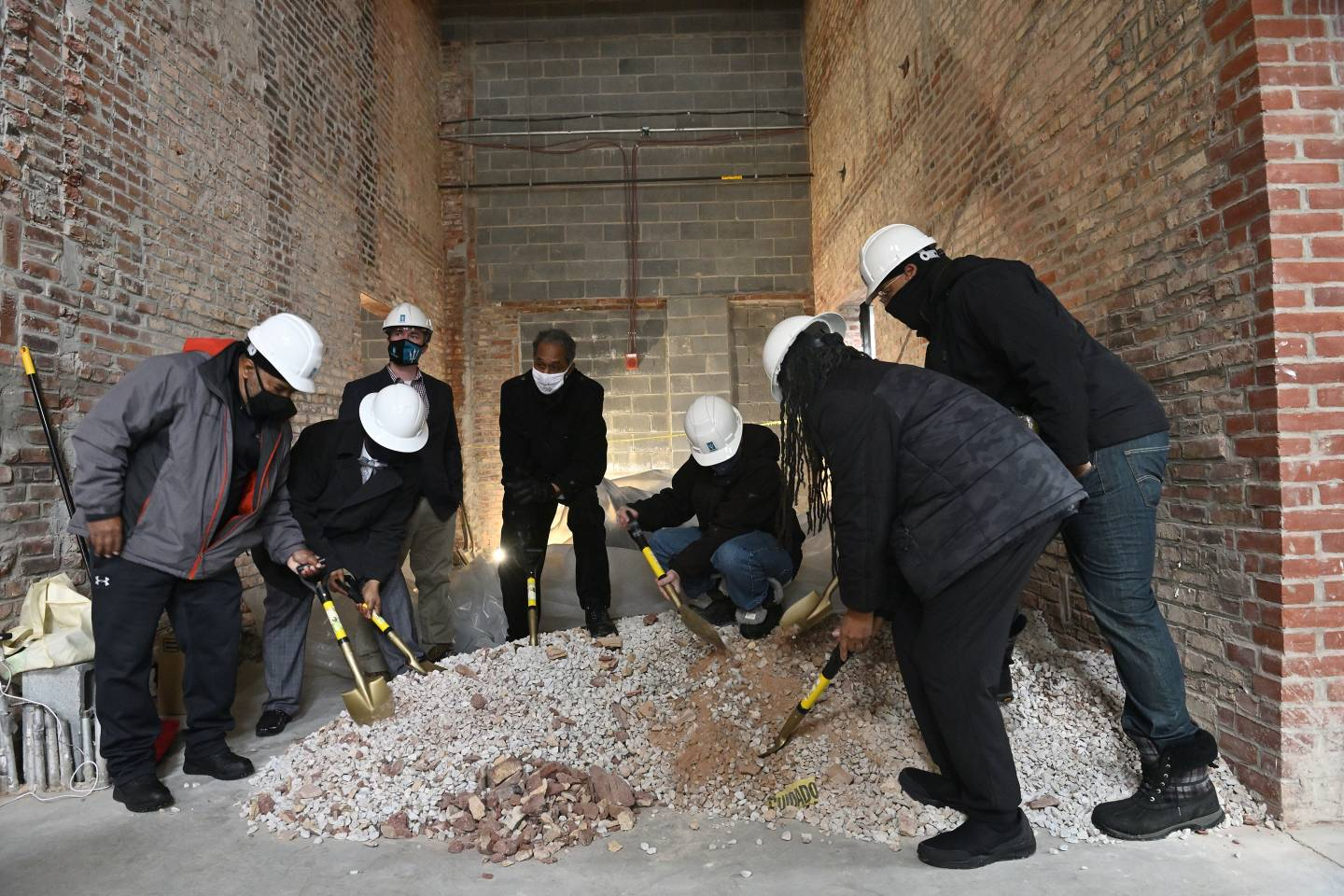 Community leaders and developers shovel brick dust in an empty row home