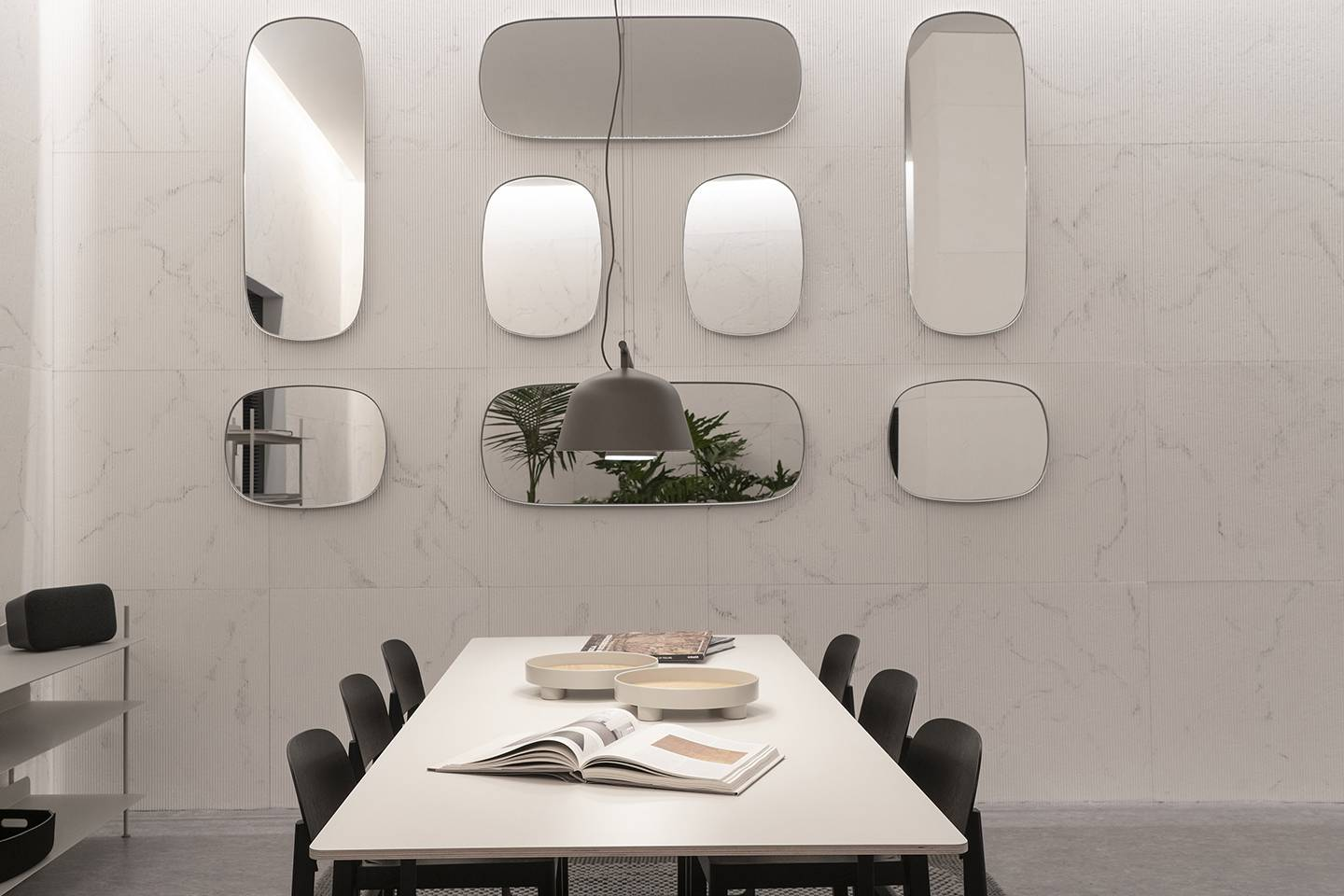 A dining room with natural marble walls, round mirrors, and sleek furniture