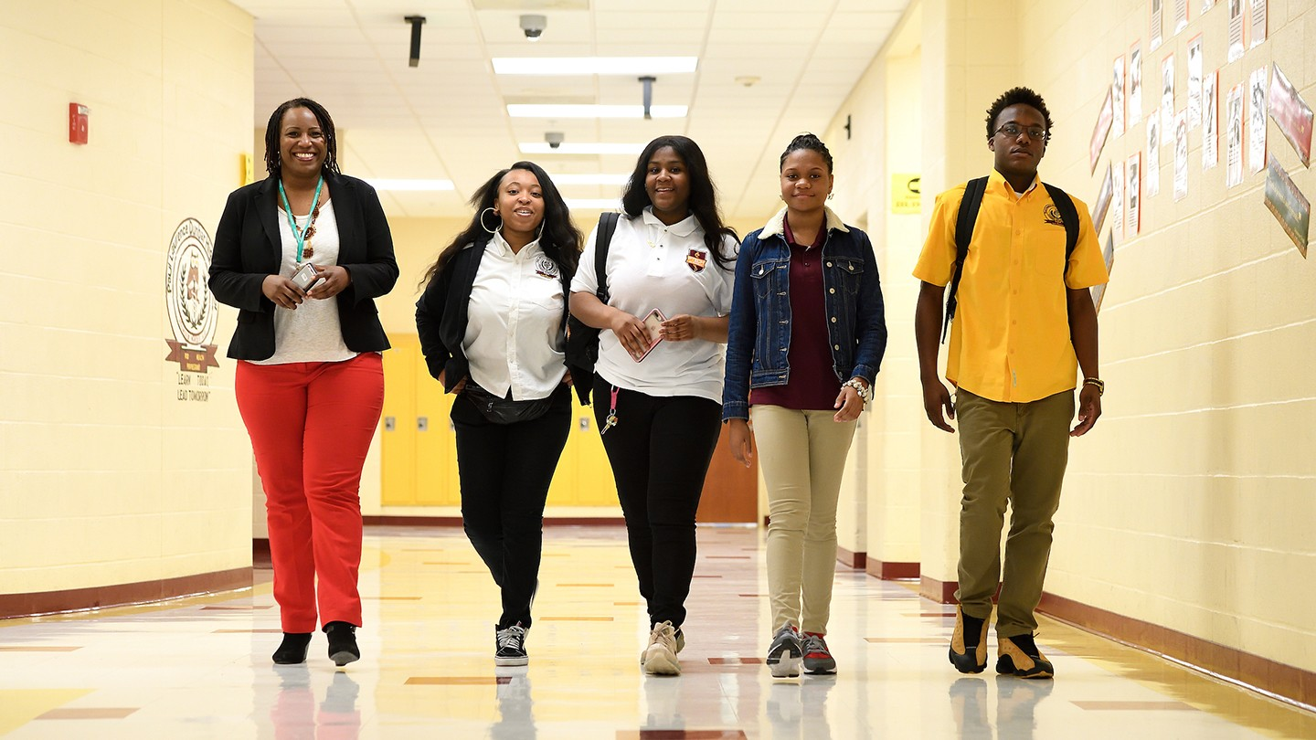 Photo shows Alexia Smith of the Johns Hopkins University Office of Community Affairs,  with Dunbar High School students Caitlun Clark, Nayonna Earl, Simone Wade and Alvin Winn