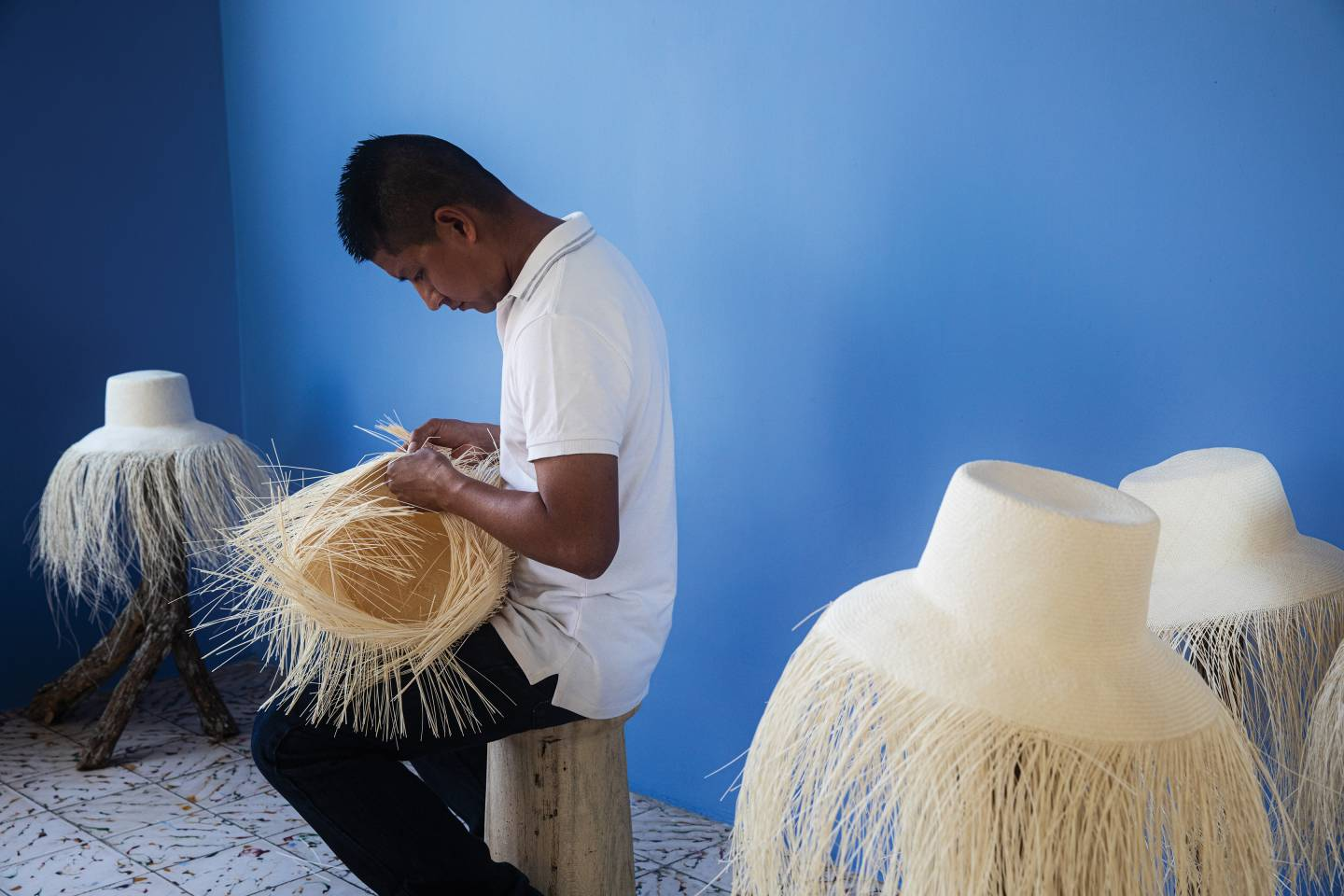 An artisan weaves a Panama hat in a workshop