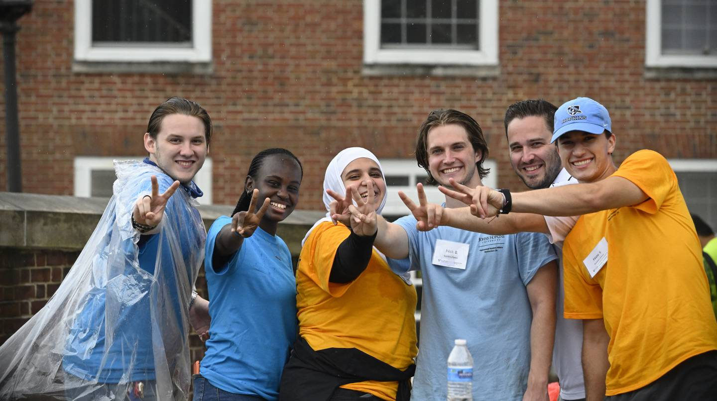 RAs give peace signs as they help new students move in