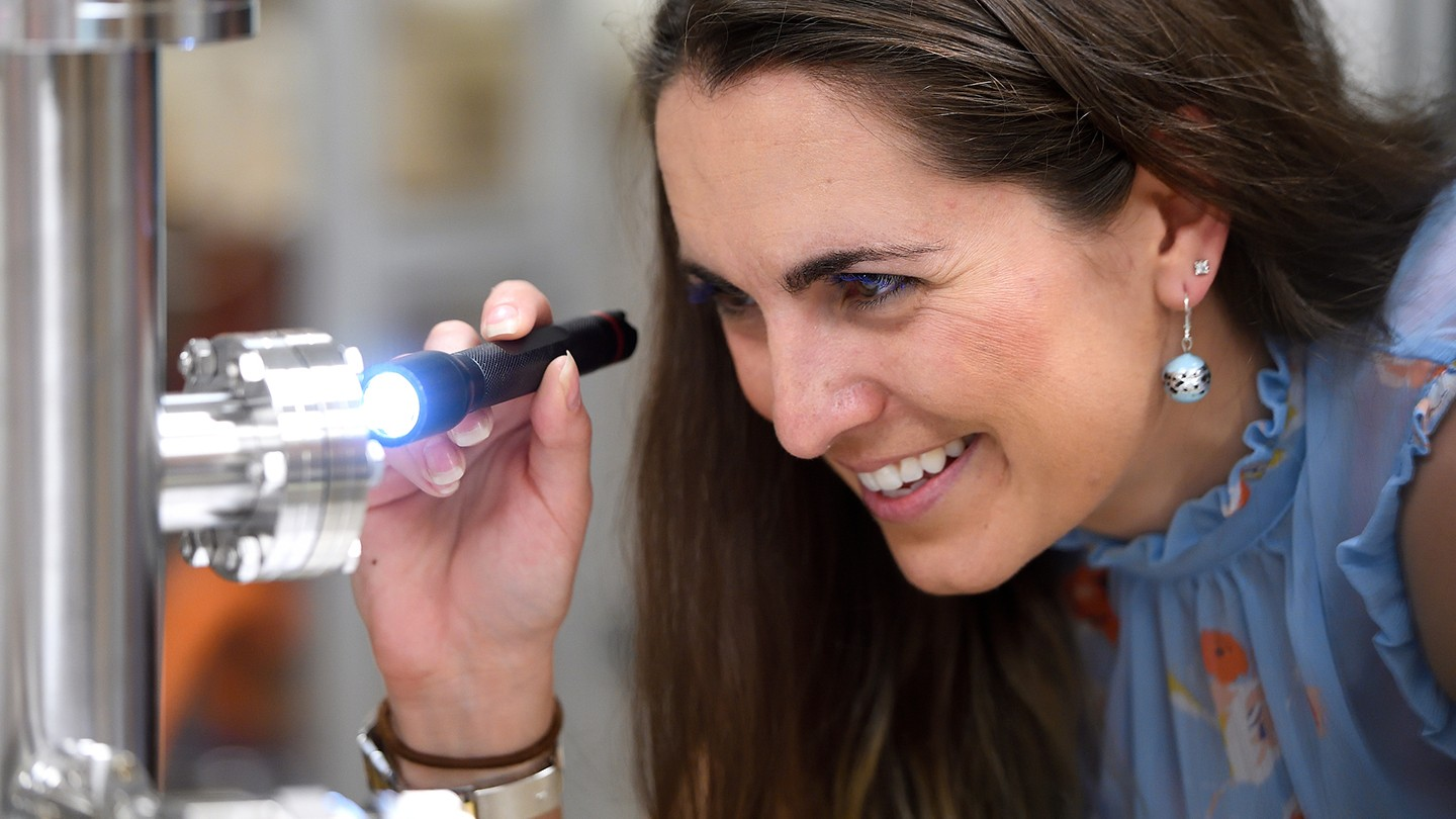 A woman uses a flashlight and what looks like a microscope