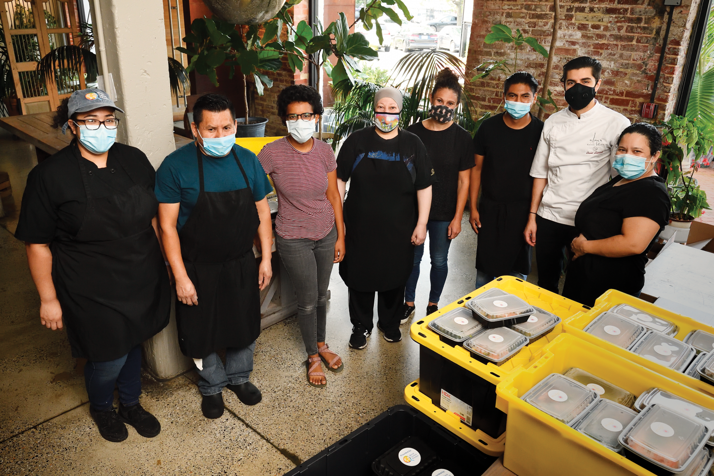 A group of masked people in a kitchen