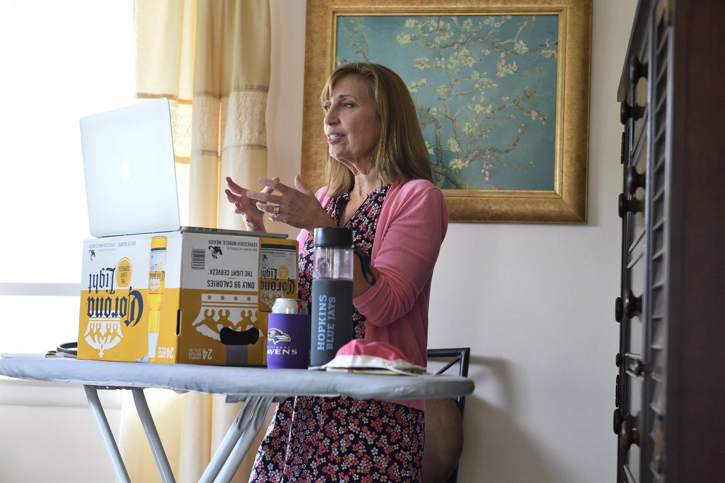 A woman teaches with her laptop propped on a beer box on an ironing board