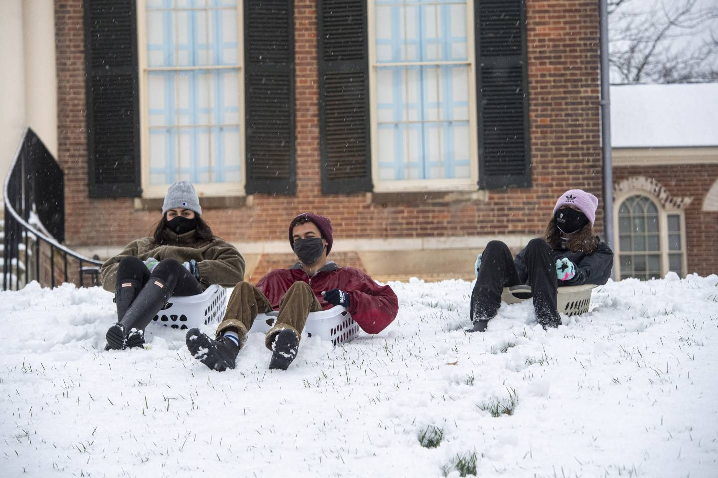 Three masked students sit in laundry baskets in the snow
