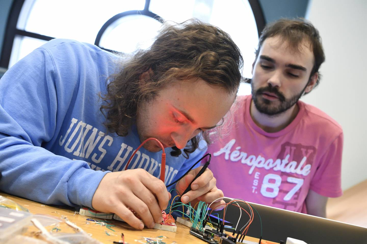 Two men build an electronic device