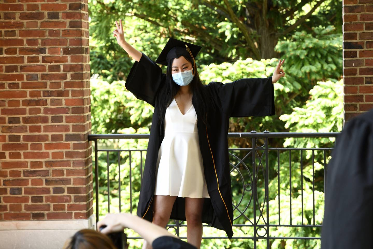 A student in cap and gown and a mask poses for a photo