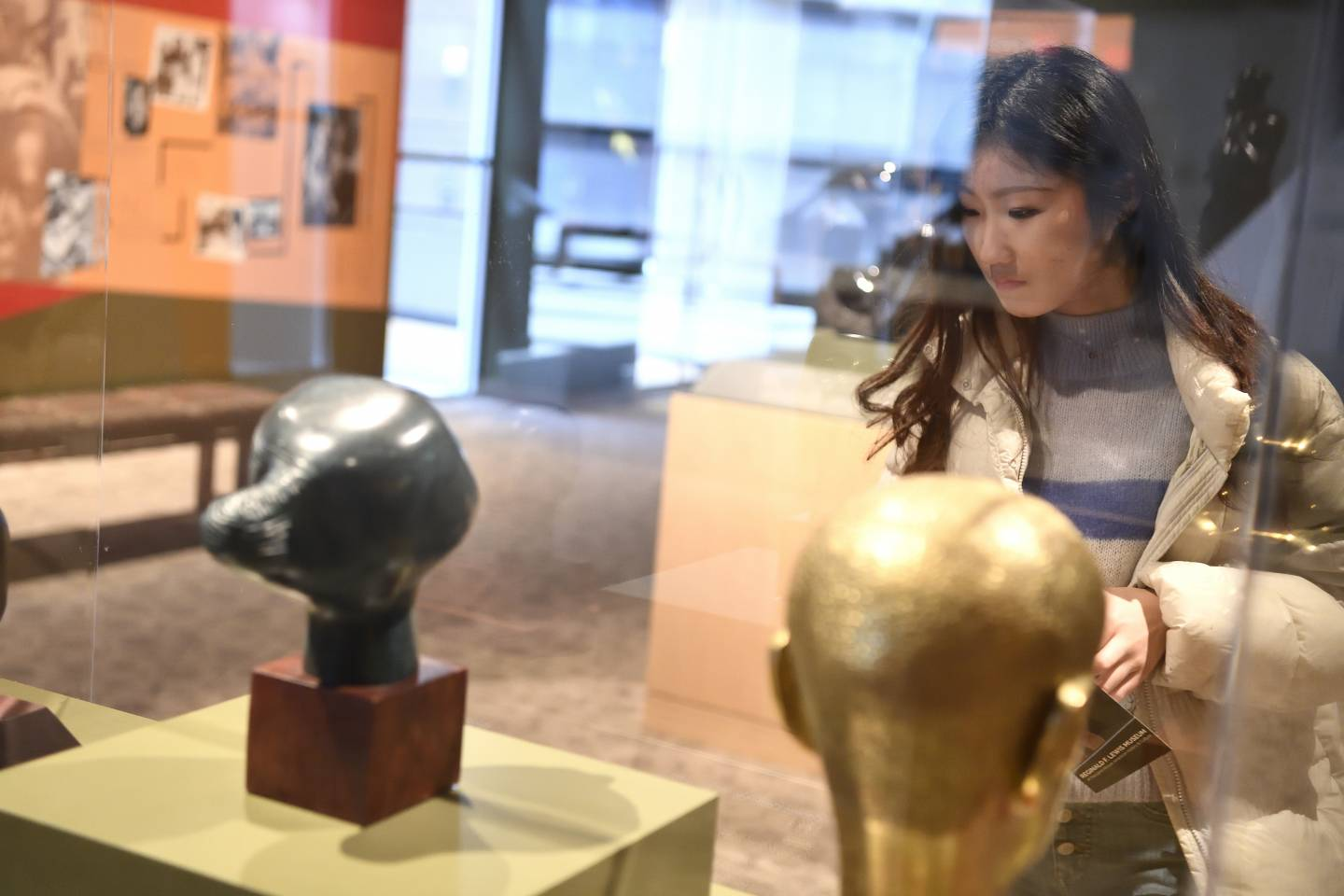 A woman examines an exhibit in a museum