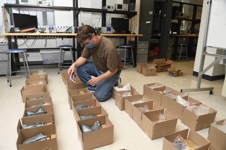 A man kneels beside open boxes
