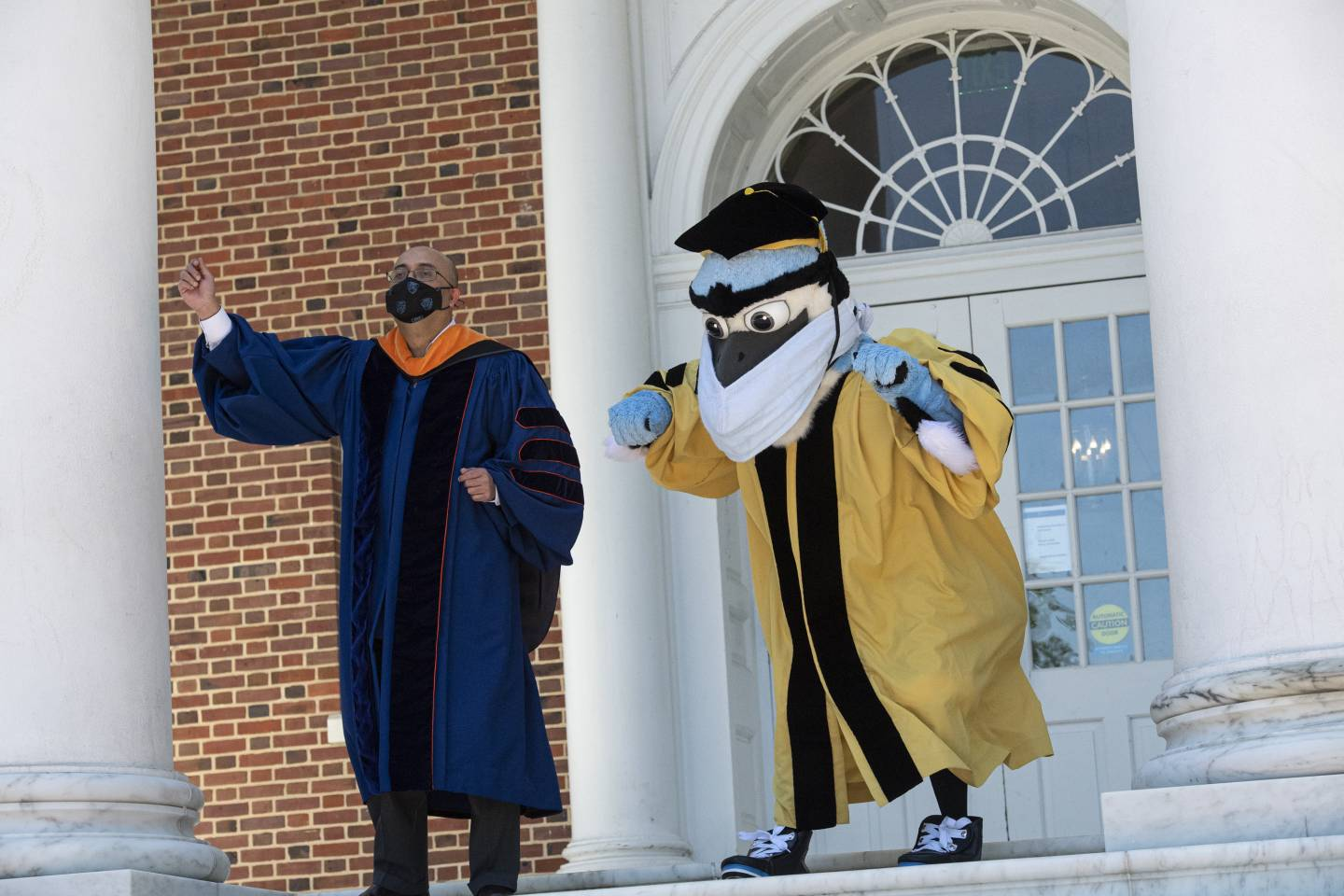 Blue Jay mascot and Provost Sunil Kumar dance on the steps of Gilman Hall