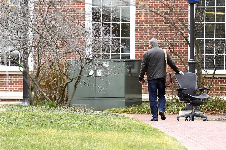 A man wheels a chair behind him as he leaves campus
