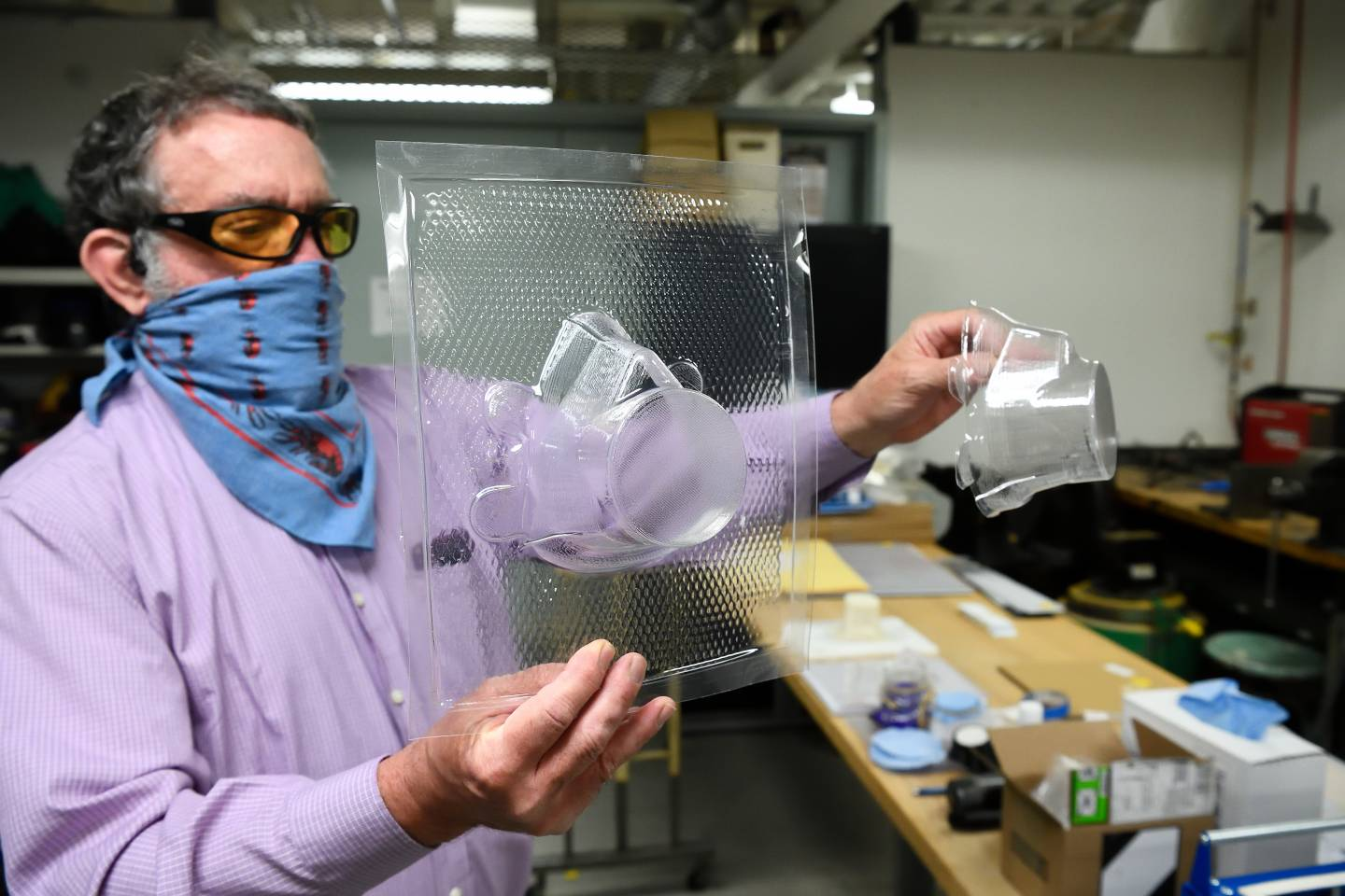 Niel Leon examines vacuum-formed pieces built for WSE's respirator mask design.