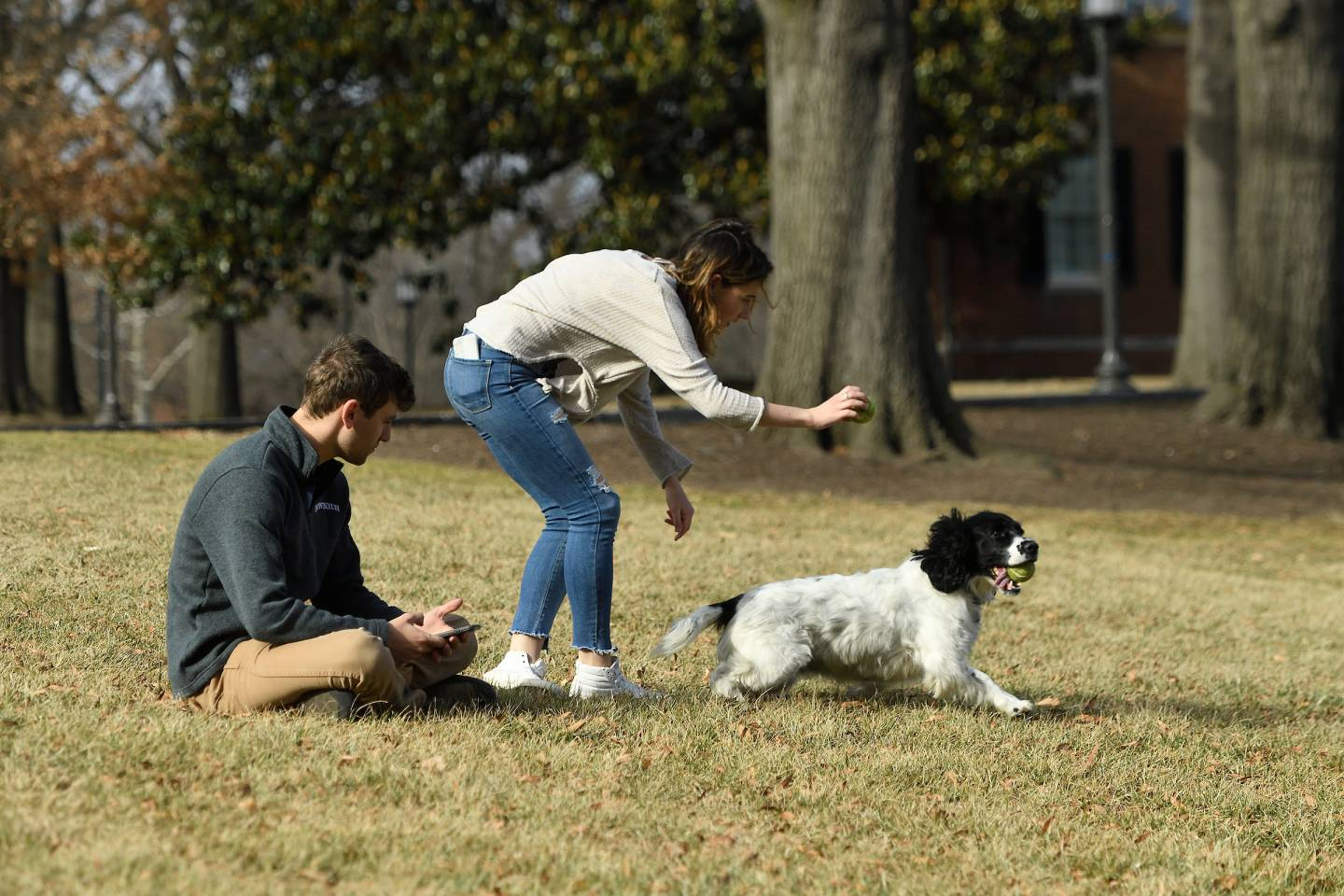 Two people play fetch with a dog