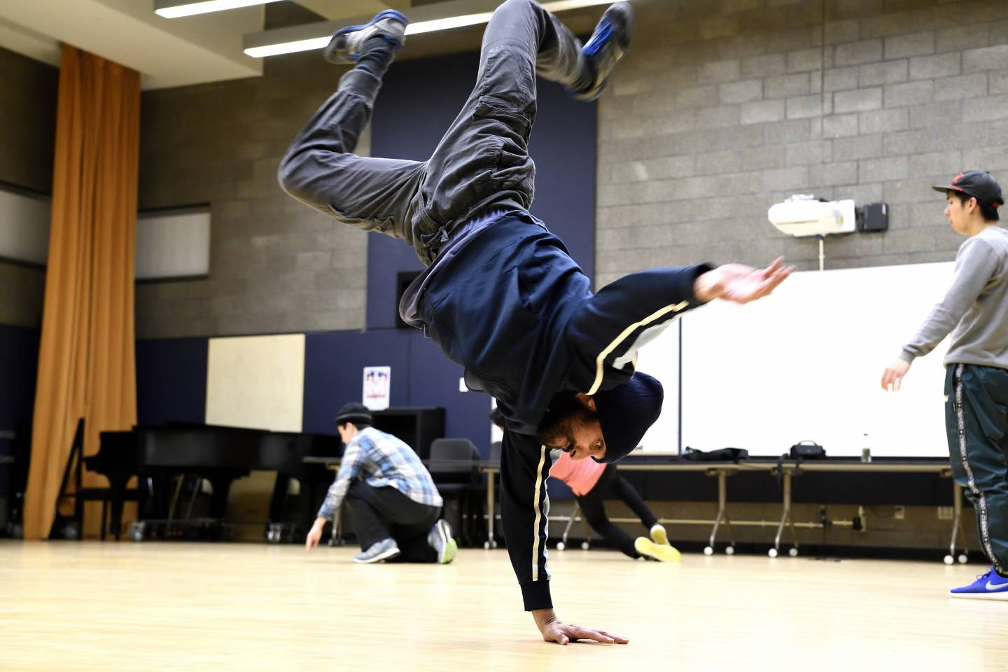 A breakdancer spins on his shoulders