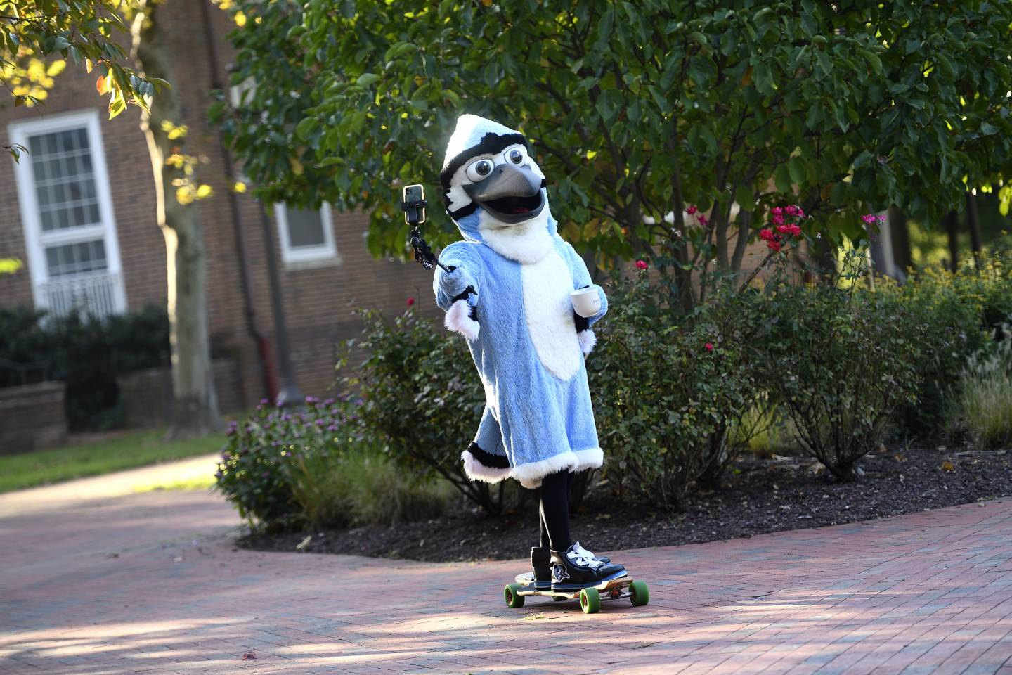 Hopkins Blue Jay skateboards with a coffee and selfie stick