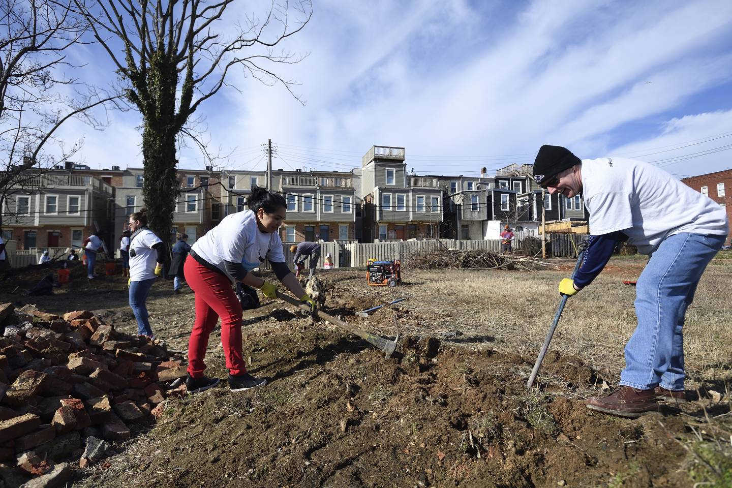 Volunteers shovel and ice pick ground in a vacant Baltimore lot