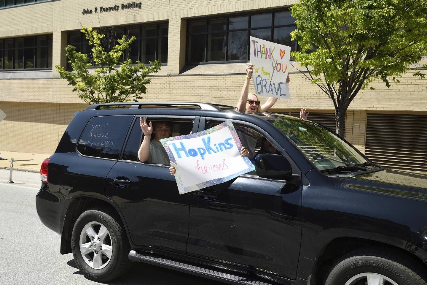 People in a car wave signs thanking health care workers
