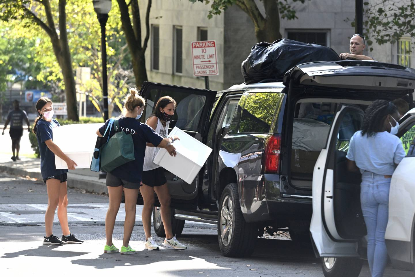 Parents and siblings unload a car during move-in