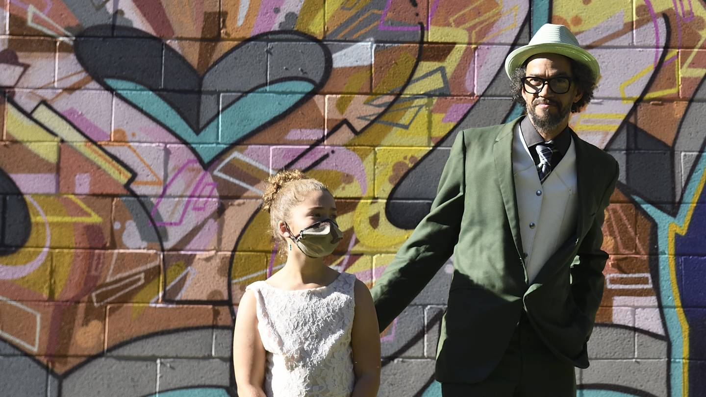 Graffiti writer Adam Stab and his daughter attend the mural unveiling in West Baltimore