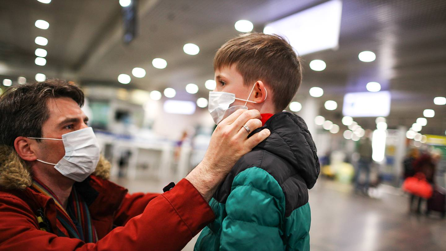 A father adjusts his son's face mask