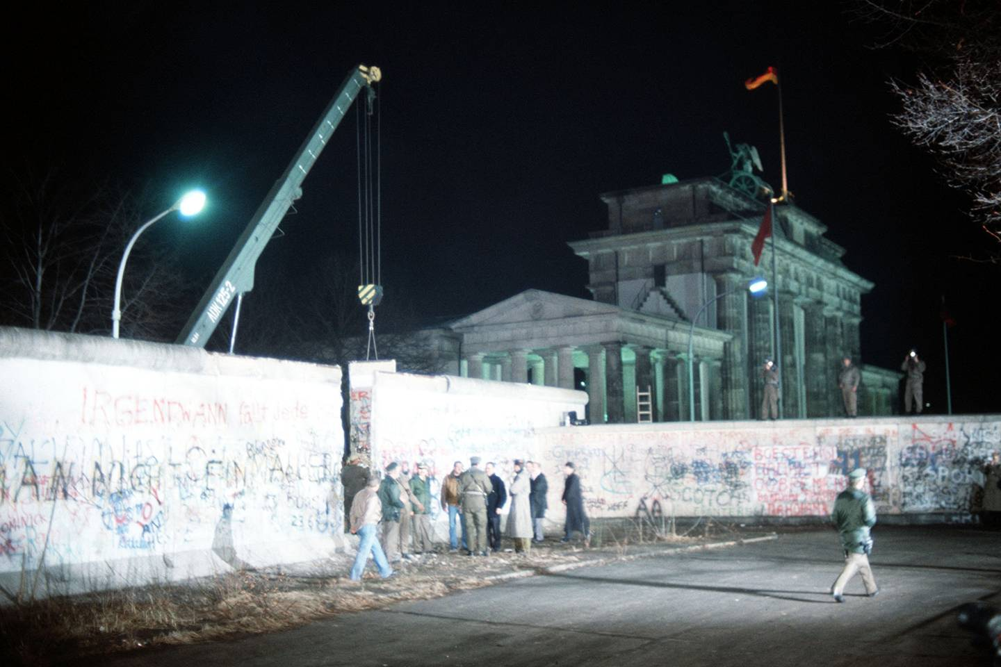A crane removes a section of the Berlin Wall