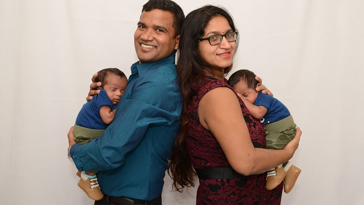Couple poses back to back for photo with their twin infants