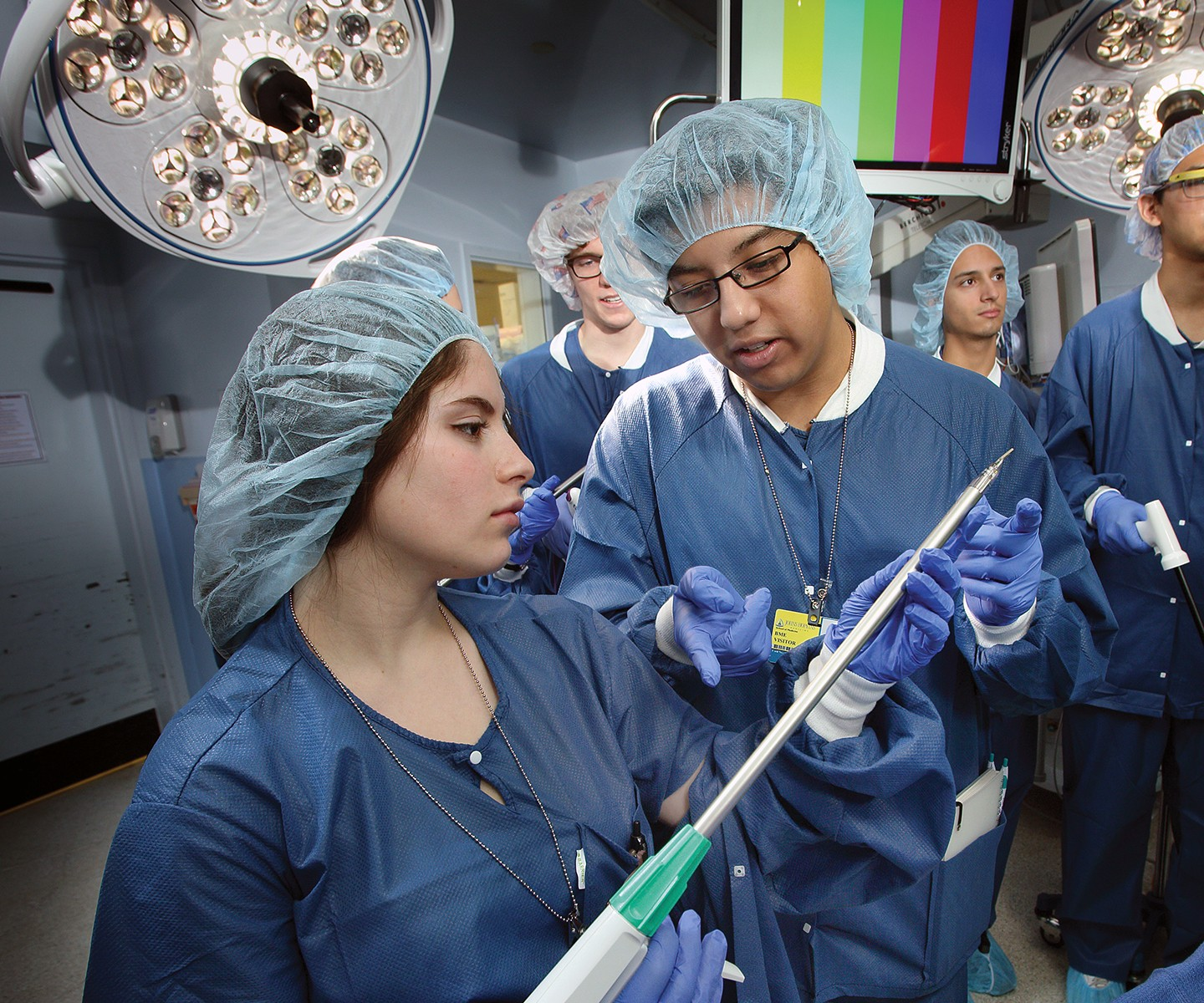 Two students in scrubs examine a medical device