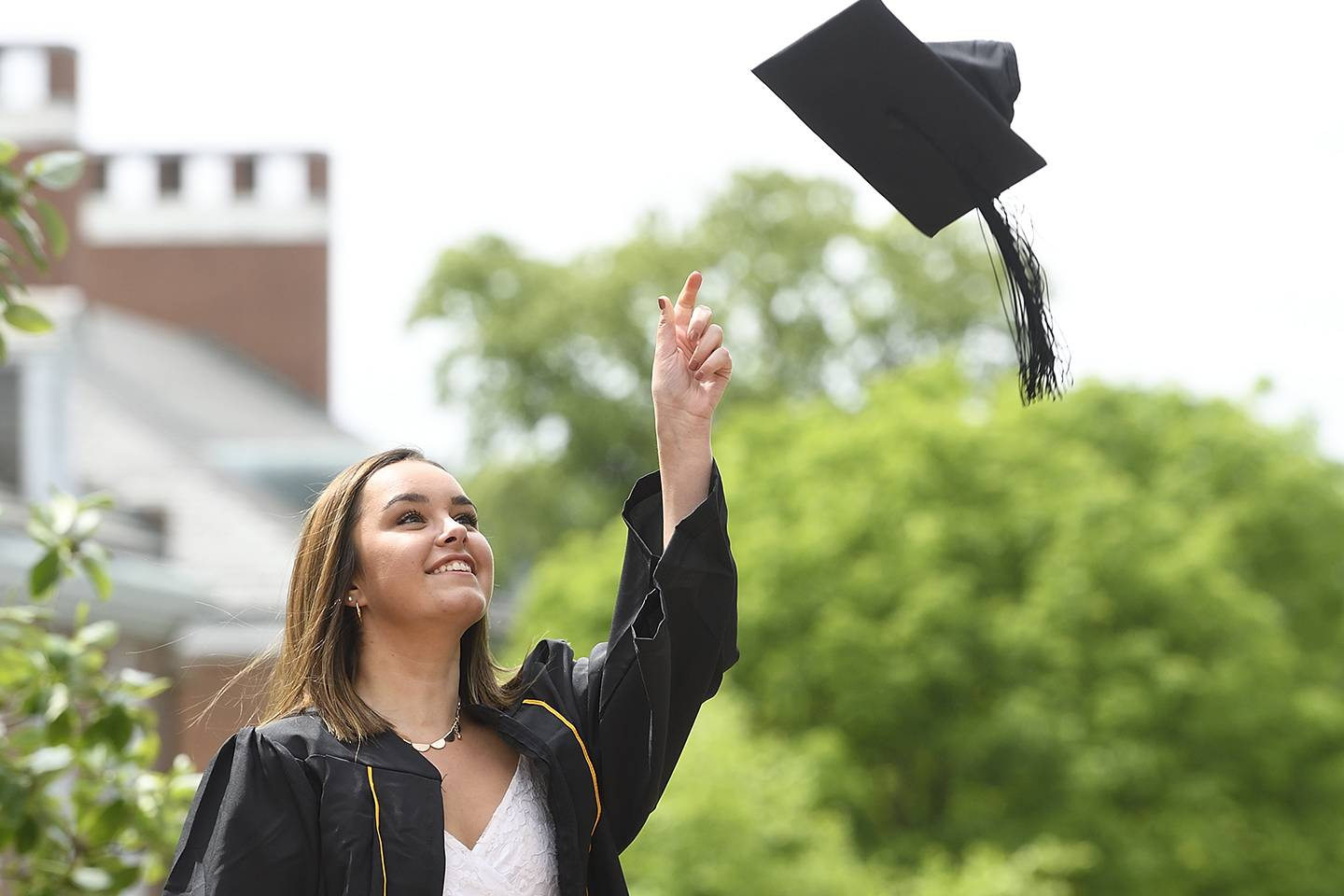 A student throws her graduation cap