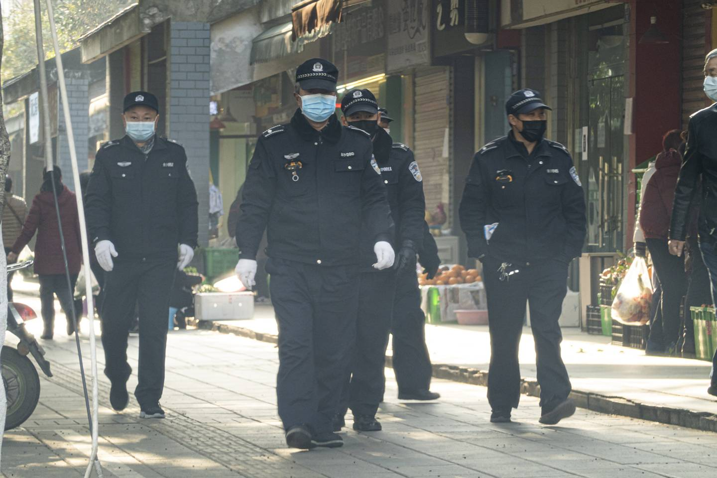 Chinese officials walk down a sidewalk