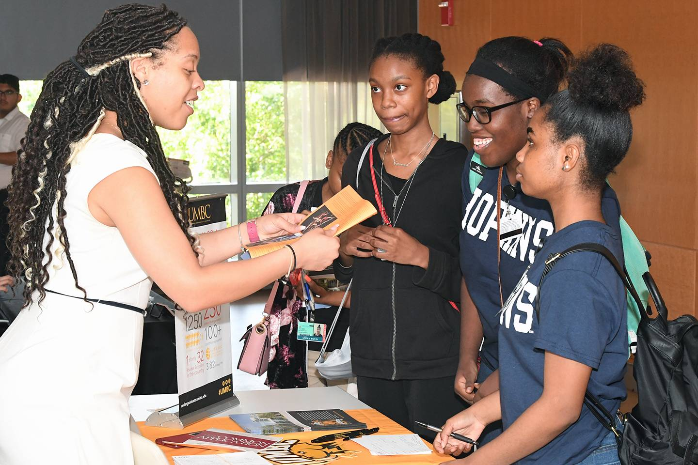 Students talk with a college rep at a college fair
