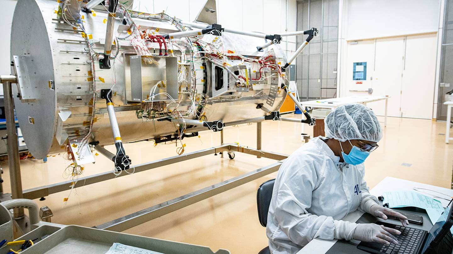 A scientist works on the Europa Clipper spacecraft