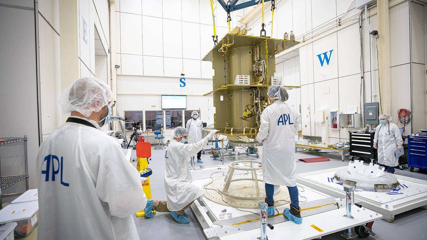 People in masks, lab coats, and booties unpack a spacecraft
