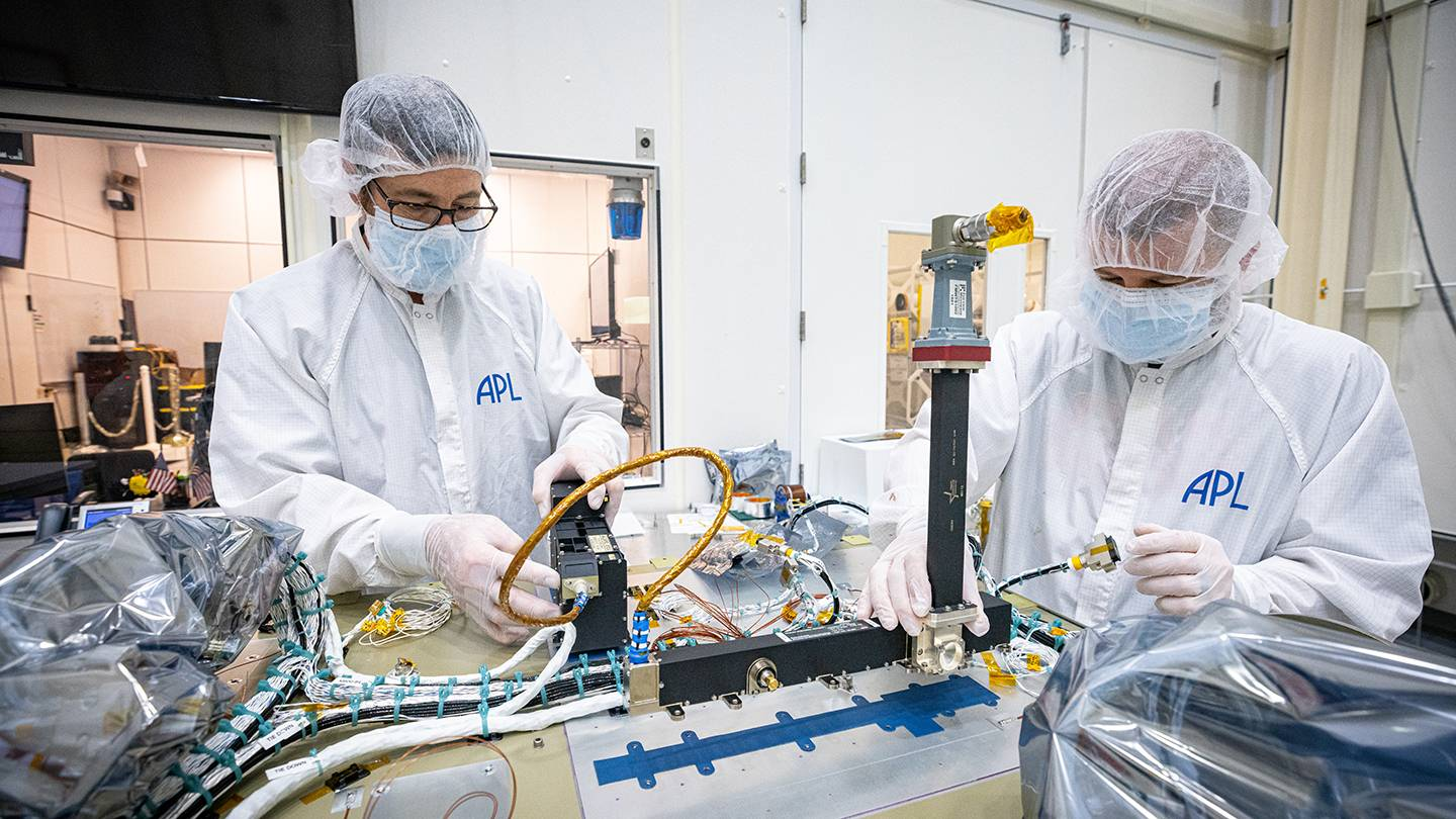 Two scientists wearing protective gear work side-by-side on a spacecraft