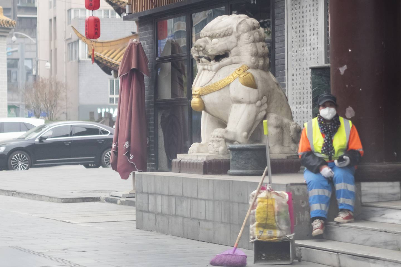 Chinese sanitation worker rests on roadside