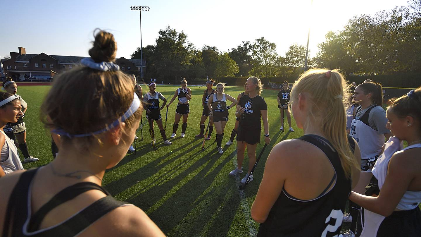 The field hockey team huddles up after practice