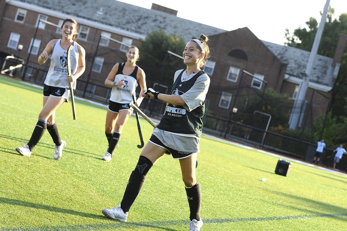 Field hockey player strides confidently across the field