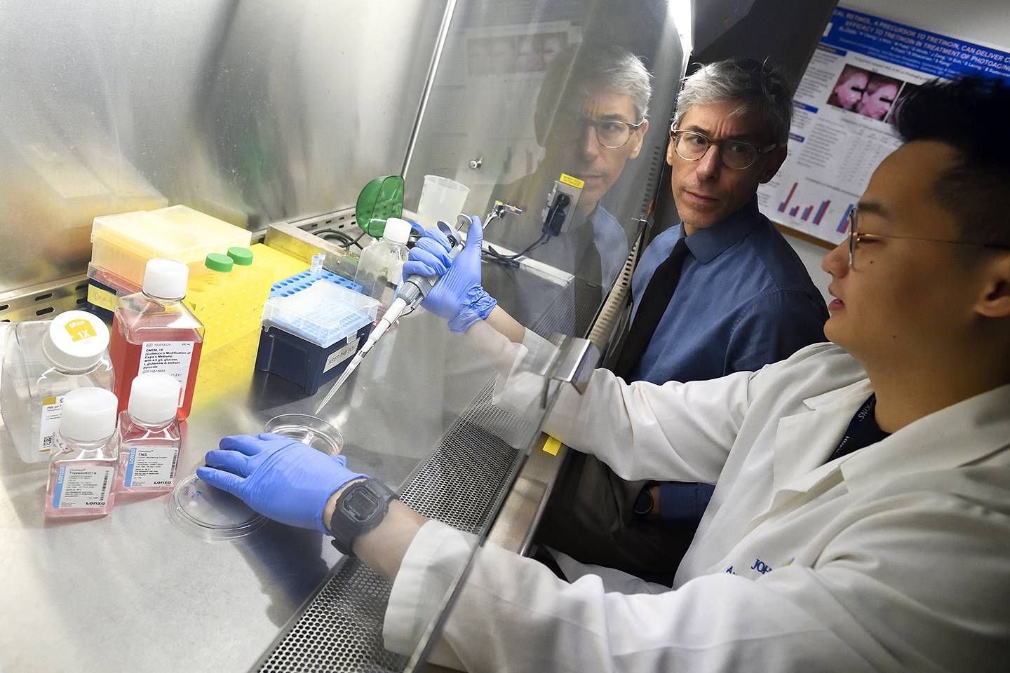 Luis Garza and a researcher work in the lab