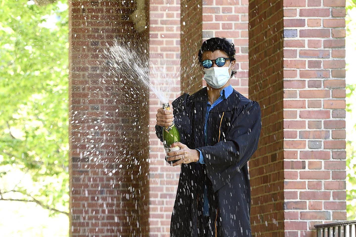 A graduate wears a mask and sprays a bottle of champagne