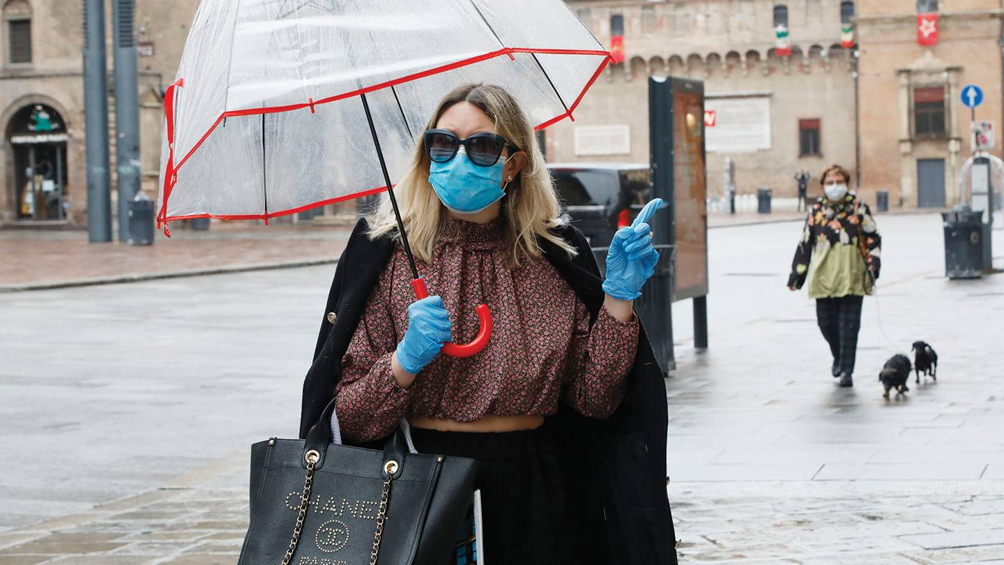 A woman with a designer handbag wears surgical gloves and a mask