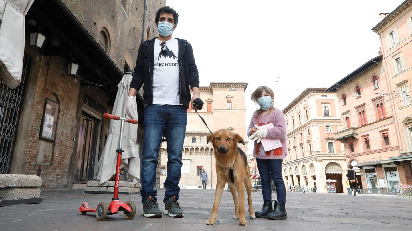 A father and daughter walk their dog in Italy