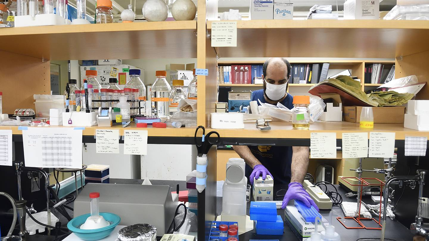 A man organizes a shelf of lab materials like gloves, chemicals, and beakers
