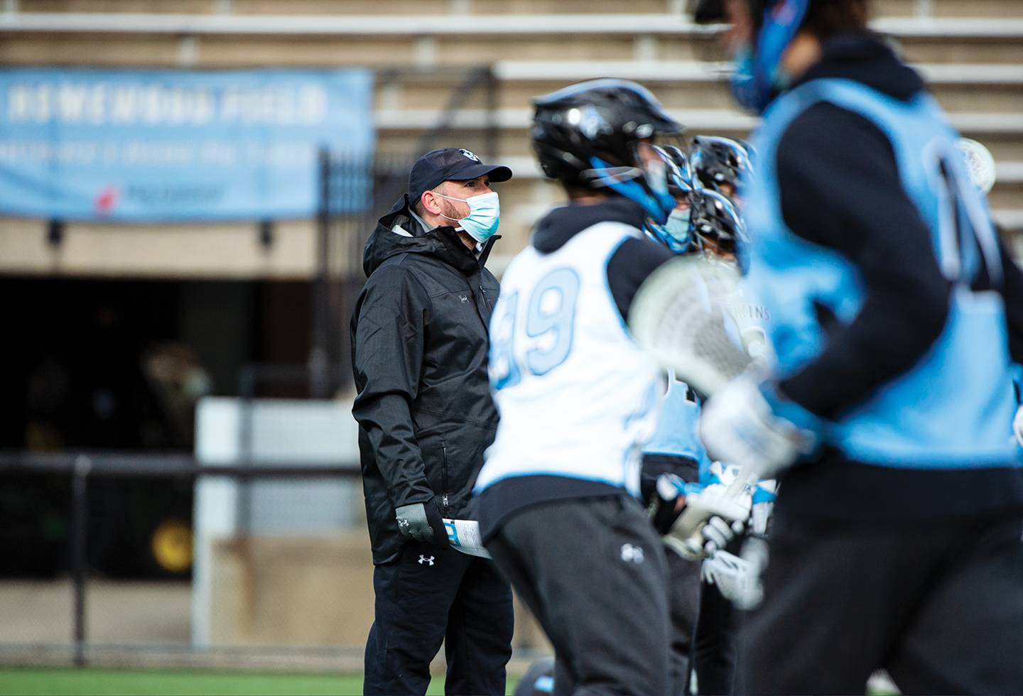 Coach Pete Milliman, wearing a face mask, watches lacrosse practice