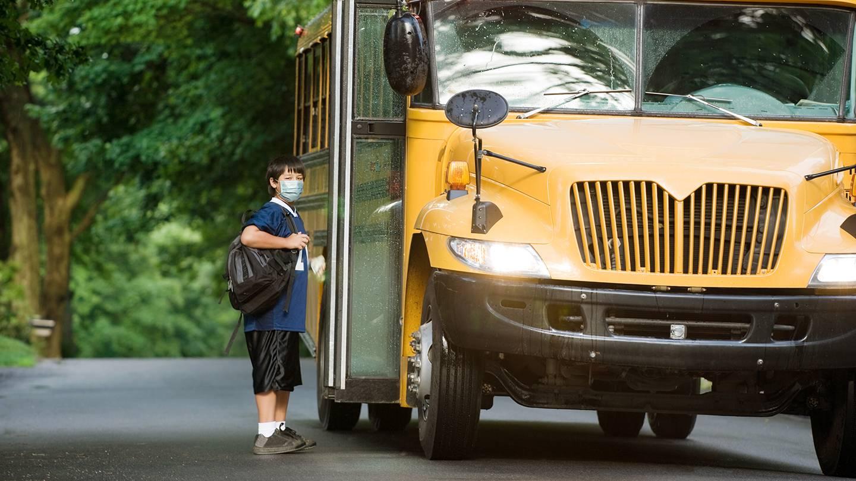 A masked boy boards a school bus