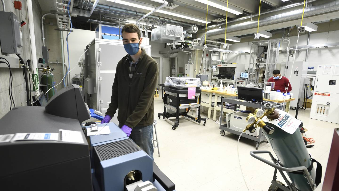 Two masked researchers work in the PARADIM lab
