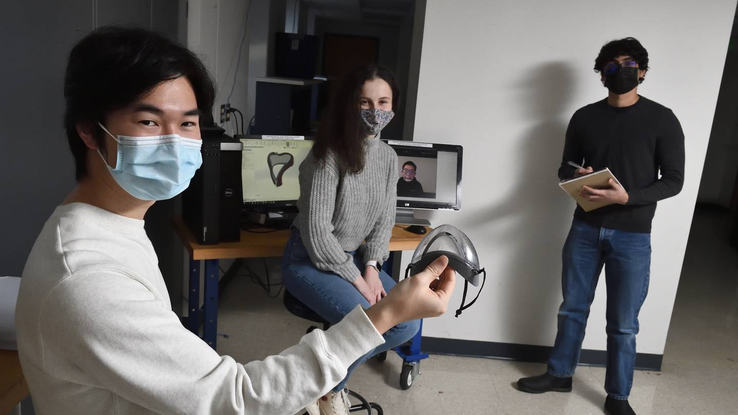 Three masked students in a lab space work with a mask prototype