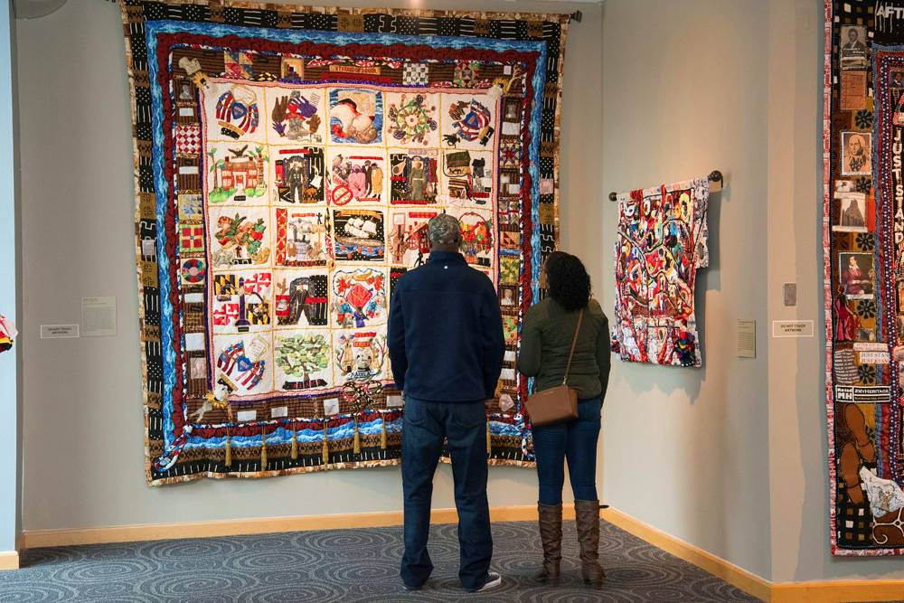 Two people stand in front of a quilt