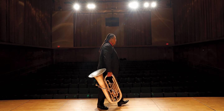 Tubist Richard White walks across stage