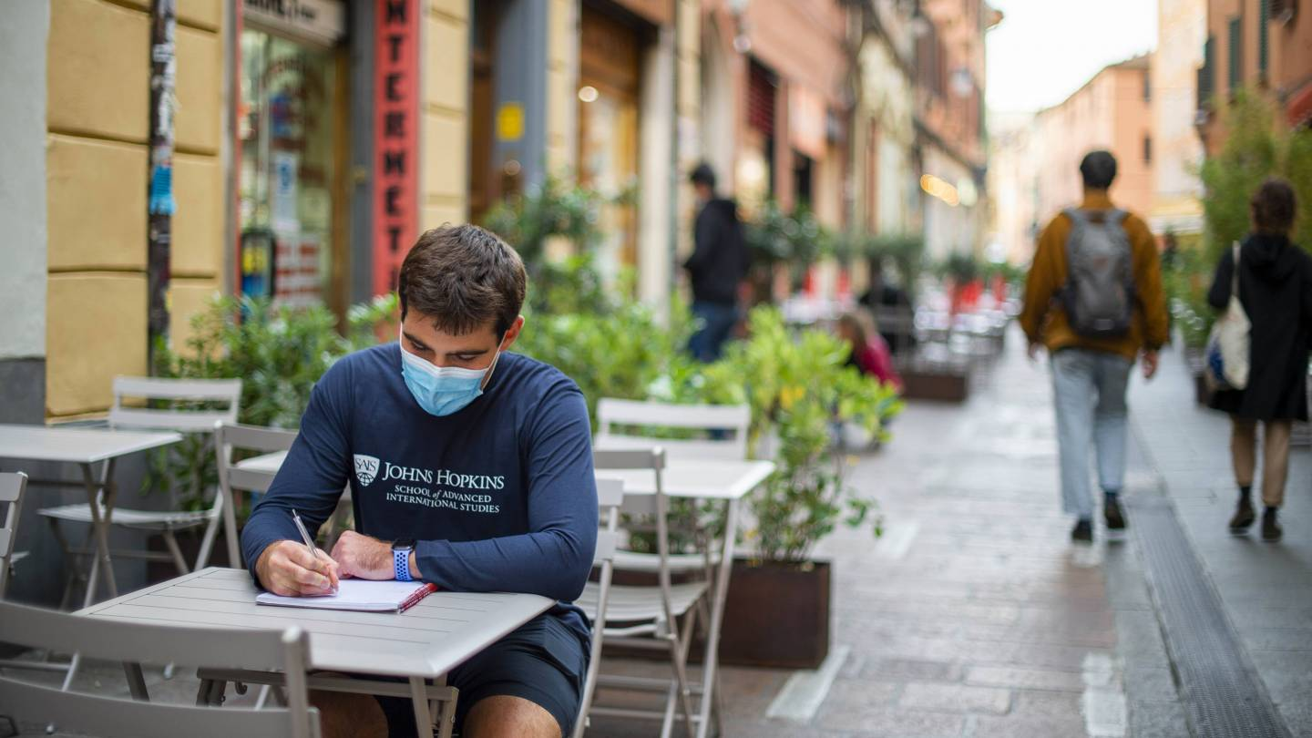 A student studies in a street cafe in Italy