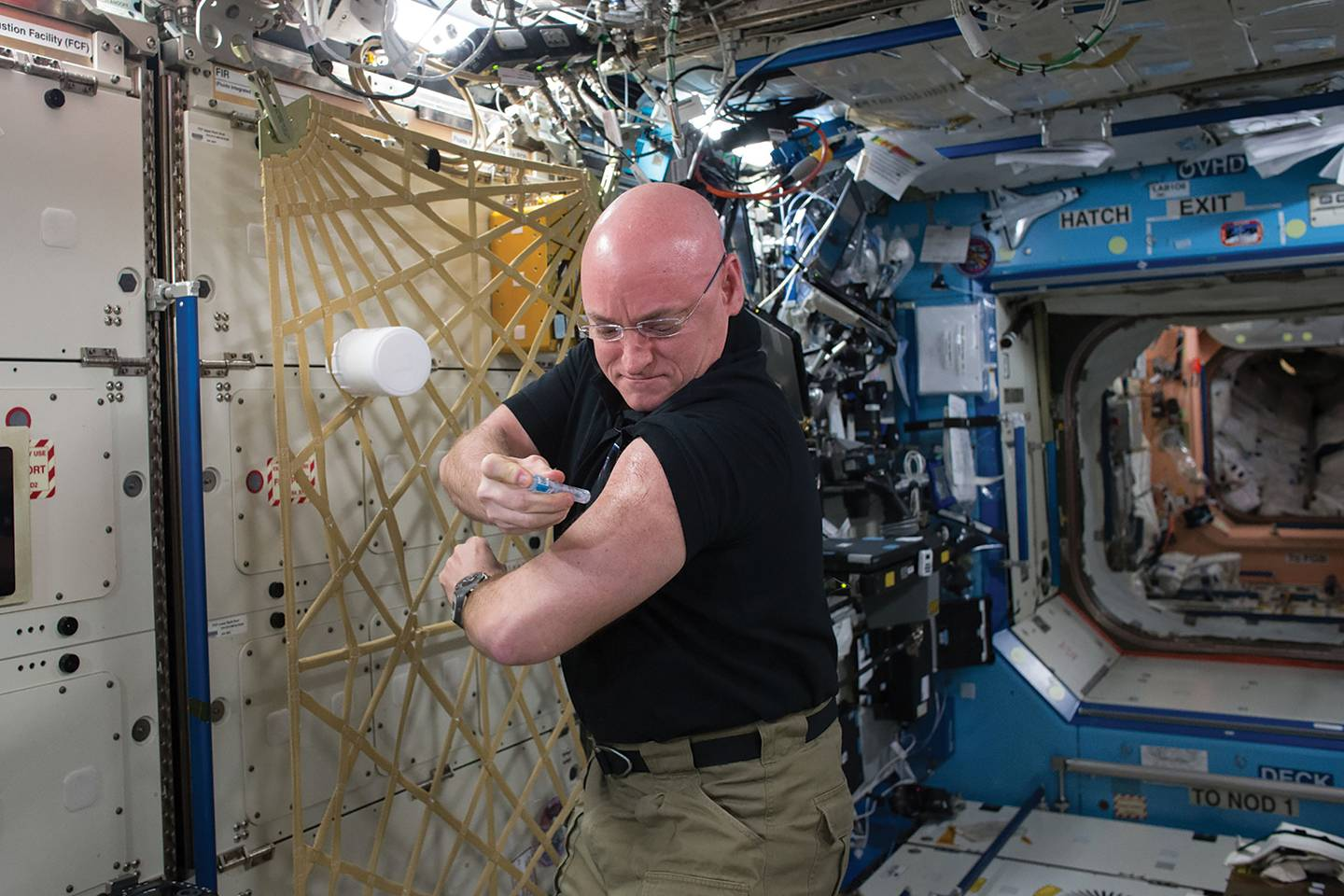 Astronaut Scott Kelly injects himself with a needle