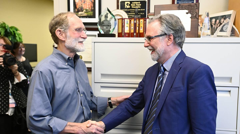 Gregg Semenza and Peter Agre shake hands